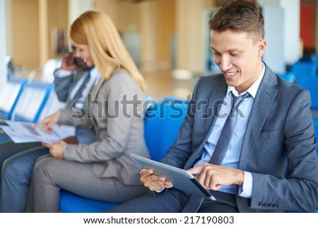 Elegant businessman networking in airport with two colleagues interacting on background - stock photo