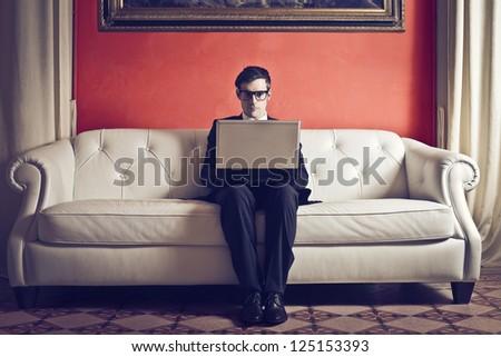 Elegant businessman on a white sofa with a laptop computer - stock photo