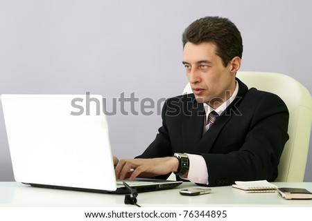 Elegant businessman sitting at desk in office - stock photo
