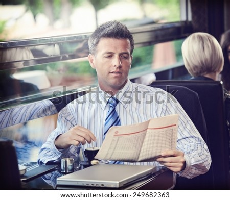 Elegant businessman traveling on luxury train, having coffee reading newspaper. vintage effect. - stock photo