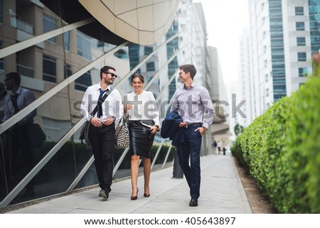 Elegant businesspeople walking in a modern city. - stock photo