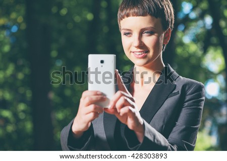 Elegant caucasian young short hair woman in formal wear taking a photo with her cell phone camera outdoors with a smile on her face - stock photo