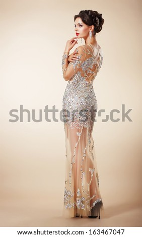 Elegant Charming Brunette in Beige Fashion Dress thinking - stock photo