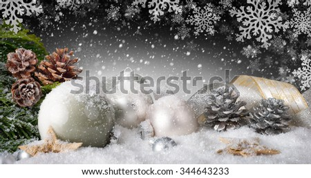 Elegant Christmas arrangement with baubles, nice ribbons, silver cones, lots of snow and ornamental large snowflakes in the dark gray background - stock photo