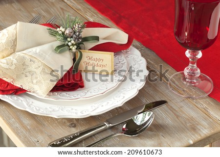 Elegant Christmas dining scene on rustic wood table with Happy Holidays card - stock photo