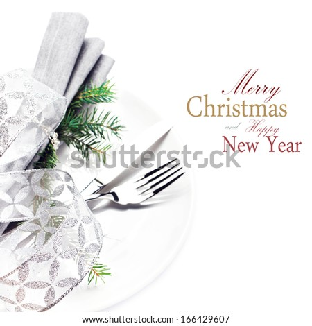 Elegant Christmas table setting place with festive ornaments on white plate isolated. Shiny golden Christmas ball, Fork and knife with copy space for greeting text, close up. - stock photo