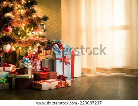 Elegant christmas tree with decorations and gifts on elegant hardwood floor. - stock photo