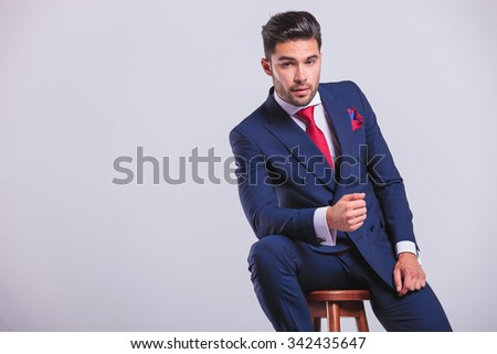 elegant corporate man leaning on a chair while sitting in studio - stock photo