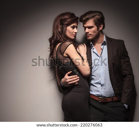 Elegant couple embracing and looking at each other. The man is holding one hand in his pocketOn dark grey background. - stock photo