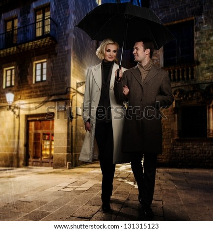 Elegant couple in autumnal coats walking in the rain outdoors at night - stock photo