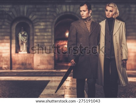 Elegant couple in coats against building facade in evening - stock photo