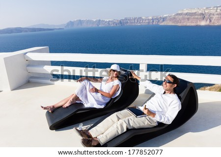 Elegant couple resting on the deck chair at the seaside terrace - stock photo