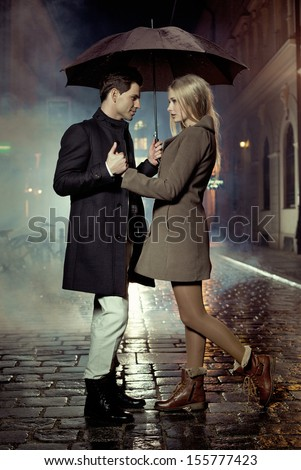 Elegant couple with umbrella on rainy evening - stock photo