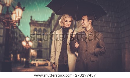 Elegant couple with umbrella walking outdoors in the rain - stock photo
