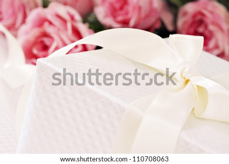 Elegant cream colored gift box with satin ribbon and bouquet of roses in background.  Macro with shallow dof and copy space.  Selective focus on corner of box and bow. - stock photo