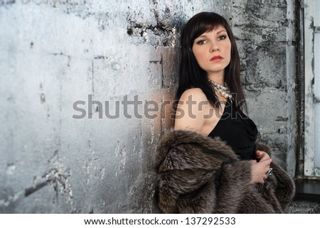 Elegant dark-haired caucasian woman wearing fur coat and jewelry, studio shot - stock photo