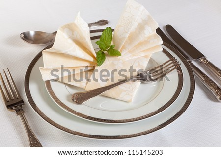 Elegant dinner table with vintage cutlery and festive napkins - stock photo