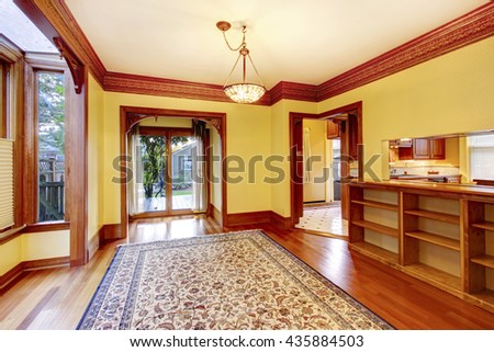Elegant empty living room with yellow walls, carved wood doorways and colorful rug - stock photo