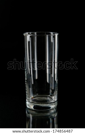 Elegant empty transparent stemmed bottle silhouetted by light reflections on a black background - stock photo