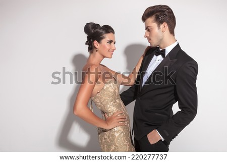 Elegant fashion couple embracing, the man holding one hand in his pocket. Looking at each other. - stock photo
