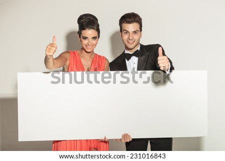 Elegant fashion couple holding a white empty board while showing the thumbs up gesture. - stock photo