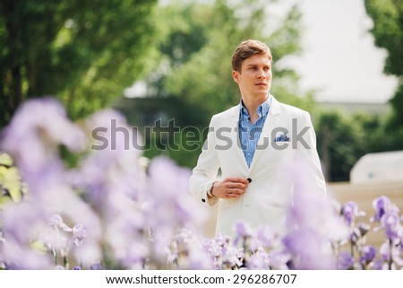 elegant fashion man in park, with trees and flowers around - stock photo