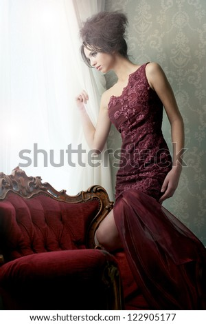 Elegant fashion model in red couture wedding dress looking out of the window in expectation. - stock photo