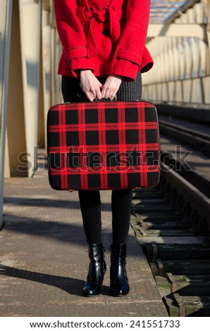 Elegant fashionable lady waiting for the train on the train station on sunny day. - stock photo
