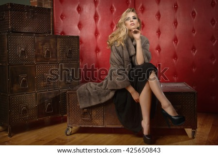 Elegant fashionable woman wearing fur cape in a dark vintage interior. Shoes is no trademark   - stock photo