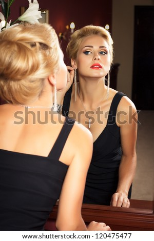 Elegant fashionable woman with diamond jewelry looks at herself in mirror. Fashion shoot. - stock photo