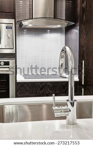Elegant faucet and sink in island counter of modern kitchen - stock photo