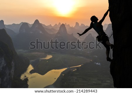 Elegant female extreme climber silhouette against the sunset over the river. China, typical Chinese landscape with mountains and river. - stock photo