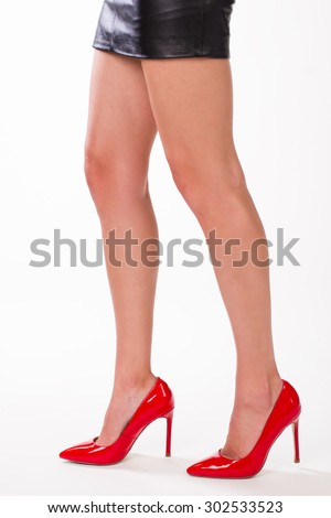 Elegant female legs in red shoes. Beautiful young legs standing in profile. - stock photo