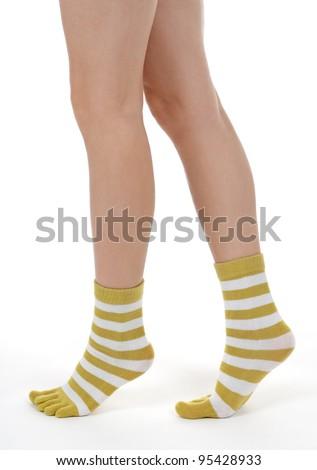 Elegant female legs in striped socks, walking on tiptoes. - stock photo