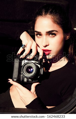 Elegant  female photographer holding a digital camera. Outdoors vertical shot . Attractive woman.  - stock photo