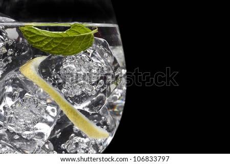 Elegant gin tonic glass on black background - stock photo