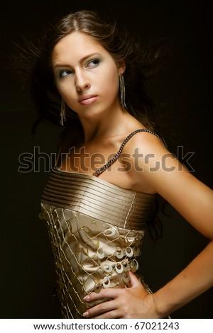 Elegant girl in gold dress, black background - stock photo