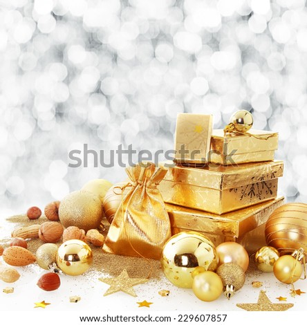 Elegant gold Christmas still life arrangement with gift boxes and a bag amongst golden metallic baubles and stars with a backdrop bokeh of falling winter snowflakes and copyspace for your greeting - stock photo