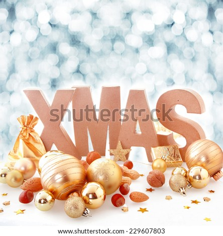 Elegant gold Xmas still life with metallic gold baubles and scattered assorted nuts in front of the word Xmas with a background bokeh of falling winter snowflakes and copyspace for your greeting - stock photo