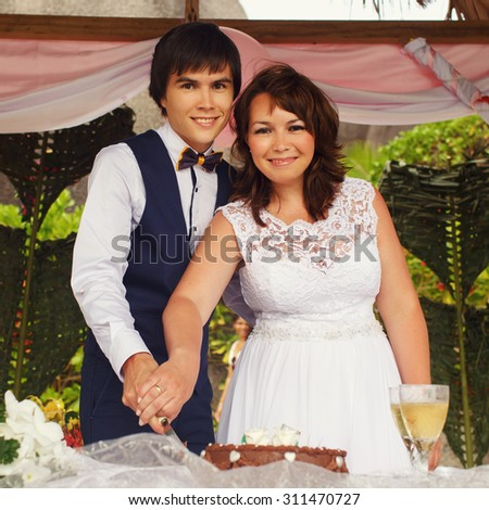 elegant gorgeous bride and groom  in the tropical bungalow cutting wedding cake, hawaiian decor, on the background of  the ocean and a beach, wedding ceremony in Seychelles - stock photo