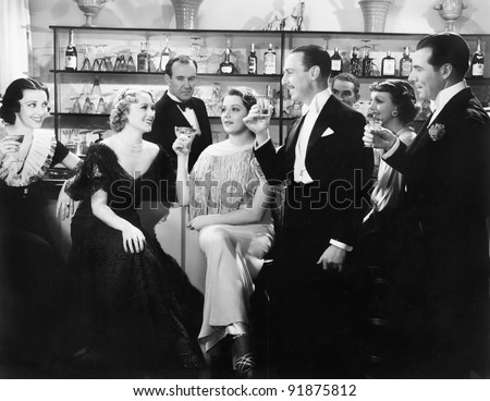 Elegant group of people at a bar toasting a woman - stock photo