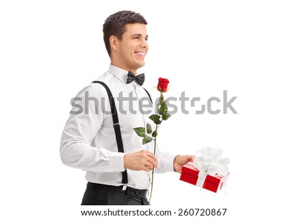 Elegant guy walking with a rose and a present isolated on white background - stock photo