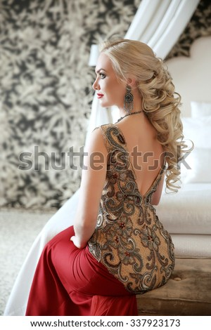 Elegant hairstyle. Beautiful blond woman in fashion red dress sitting on modern sofa at luxurious interior apartment with furniture. - stock photo