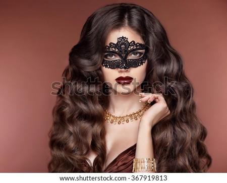 elegant hairstyle. Beautiful brunette girl model. Fashion golden jewelry. Beauty glamour woman wearing in venetian masquerade carnival mask. - stock photo
