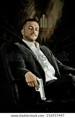 Elegant handsome latin man gangster mafia spy hitman assassin with closed eyes sitting in a chair holding a gun over dark background - stock photo