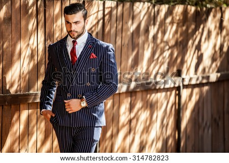 Elegant handsome man in classical blue suit poses near  wooden fence. - stock photo