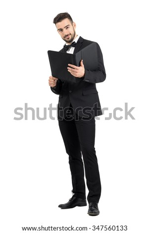 Elegant handsome man in suit reading paper document folder looking at camera. Full body length portrait isolated over white studio background.  - stock photo