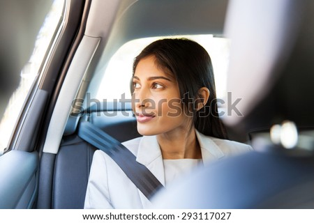 elegant indian business executive looking out of a car window - stock photo