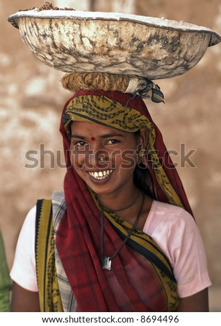 Elegant Indian woman laborer carrying a heavy metal bowl filled with plaster on her head. The bowl is balanced with the help of a coil of rope  - stock photo