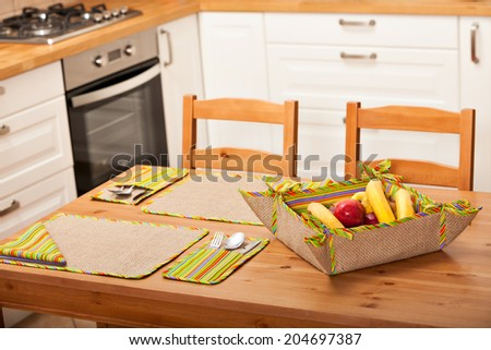 Elegant kitchen table setting with striped pattern fabrics and a bowl of bananas and apples - stock photo